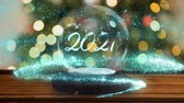 snow globe : Animation of number 2021 in white letters on a snow globe, blue shooting star and Christmas tree in the background