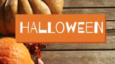 oslava : Animation of the word Halloween in white letters on an orange banner with pumpkins on wooden floorboards in the background Dostupné videozáznamy