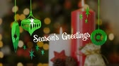 フリッカー : Animation of the words Seasons Greetings written in white letters with Christmas baubles drawn in green, in front of defocused Christmas tree 動画素材