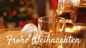 color flicker : Animation of the words Frohe Weihnachten written in white with drink being poured with Christmas tree in the background Stock Footage