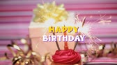 kelime : Animation of the words Happy Birthday in yellow and white letters with candle and sparklers being lit on cupcake with a present on striped background Stok Video