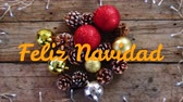 フリッカー : Animation of the words Feliz Navidad written in orange over Christmas decorations in the background