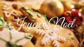 フリッカー : Animation of the words Joyeux Noᅢᆱl written in white with Christmas cookies in the background