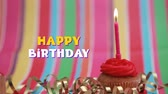 резервный : Animation of the words Happy Birthday in yellow and white letters with candle on cupcake on striped background