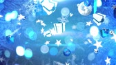 Animation of falling white icons of Christmas gifts, stars, snowflakes and baubles, falling against a blue background with defocussed circles of flashing light Stockvideo