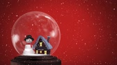 vállkendő : Animation of a snowman standing beside a snow covered cottage in a snow globe, with falling snow against a red background Stock mozgókép