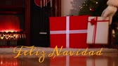 Animation of the words Feliz Navidad written in orange over sitting room at Christmas time with Santa Claus leaving presents in the background