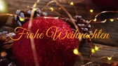 Animation of the words Frohe Weihnachten written in orange with Christmas decorations in the background