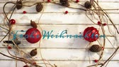 kelime : Animation of the words Frohe Weihnachten written in blue over Christmas decorations with red baubles and pine cones