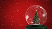 zonsondergang : Animation of a decorated Christmas tree in a snow globe, with falling snow against a red background Stockvideo