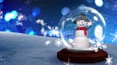 vállkendő : Animation of a waving, blinking snowman in a snow globe, with snow covered ground, falling snowflakes and defocussed circles of blue light in the background