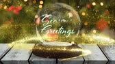 gwiazda : Animation of the words Seasons Greetings written in blue letters on a snow globe, yellow shooting star and Christmas tree in the background Wideo