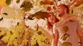 kasım : Animation of colourful leaves falling in autumn in a forest with a young couple embracing and holding balloons