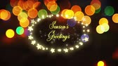 gwiazda : Animation of the words Seasons Greetings written in yellow letters in an oval frame of glowing star shaped fairy lights on with defocused flickering lights on black background Wideo