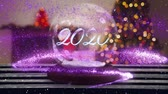 gwiazda : Animation of number 2020 written in white letters on a snow globe, purple shooting star and Christmas tree in the background