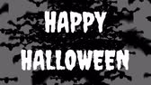 суеверие : Animation of the words Happy Halloween written in white with lots of black bats flying to the foreground, on a grey background Стоковые видеозаписи