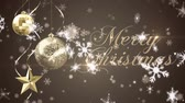 ornamenti oro : Animation of the words Merry Christmas written in gold in front of baubles and snowflakes
