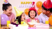 oslava : Animation of the words Happy Birthday in yellow and white letters with couple and their young daughters in party hats at a birthday party in the background