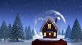 oslava : Animation of a snow covered cottage with Christmas lights on it in a snow globe, with a countryside scene with trees and and falling snow against a blue sky in the background