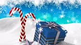 zdziwienie : Animation of snow falling, blue Christmas present and two candy canes with snow on blue background