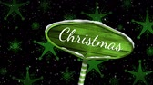 falling stars : Animation of the word Christmas written in white on green wooden sign board with snow falling and green snowflakes on black background