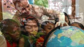 ответственность : Animation of female teacher and multi-ethnic school children using globe at school with trees in the foreground
