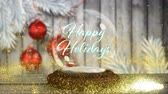 bombki : Animation of the words Happy Holidays written in blue letters in Christmas snow globe with shooting star in yellow, Christmas baubles and snow falling on wooden boards and white background