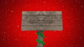 decoração do natal : Animation of wooden sign board with Christmas decorations sand now falling on red background