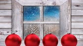 素朴な : Animation of winter scenery seen through window with snowflakes falling in countryside with four red Christmas baubles in the foreground