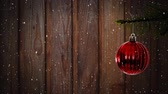 csecsebecse : Animation of snow falling with red Christmas bauble on wooden background