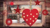 falling stars : Animation of winter scenery seen through window with snowflakes falling in countryside with Christmas decorations hanging in the foreground Stock Footage