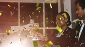 flet : Animation of group of multi-ethnic businessmen and businesswomen celebrating success and making a toast with glasses of champagne with golden confetti in the foreground Wideo