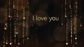 te amo : Animation of the words I Love You written in brown letters with gold shimmering lights in the background