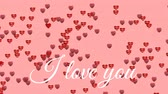 te amo : Animation of the words I Love You written in white text, with red and pink heart shaped balloons floating left to right on a pale pink background