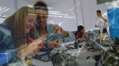meninos : Animation of two female engineering students working on an project in a laboratory, male teacher talking to students in the background, data processing and network of connections moving in the foreground. Environment and eco friendly car engineering, Stock Footage