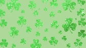 trevo : Animation of St Patricks Day multiple shimmering green shamrocks falling in slow motion on light green background. Celebration of Irish culture concept digitally generated image.