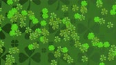 trevo : Animation of St Patricks Day pattern of multiple rows of green shamrocks with a group of multiple moving green clover leaves on dark green background. Celebration of Irish culture concept digitally generated image.