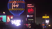 Голливуд : 4K ES: The Las Vegas Strip skyline featuring the bright lights, neon signs, and digital marquees of The Paris Hotel, Planet Hollywood, and The MGM Grand hotels, casinos, and luxury resorts. Circa 2016
