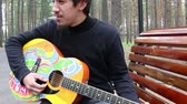 gipsy : young man and guitar in hippie style and man smokes a cigarette in the forest