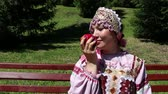 sorts : Girl in Russian national dress sniffing a red apple