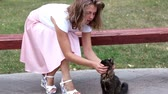 esfarrapado : The girl in the pink skirt stroking black cat