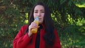 vinte anos : Girl in a red coat drinking orange juice