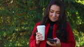 vinte anos : Girl drinks coffee and rewritten through a smartphone