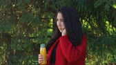 vinte anos : Girl in a red coat talking by mobile phone Stock Footage