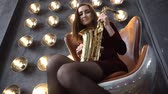 trumpet : Girl in dress with saxophone sitting on swivel chair in retro room