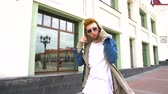 folga : Portrait of a young red haired man in stylish clothes walks at the town and take off his sunglasses. Vídeos