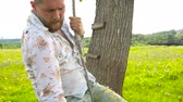 тридцать : Handsome bearded man with a beard on a swing Стоковые видеозаписи