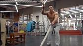 undulation : Strong man working out with Battle Ropes in a gym. Stock Footage