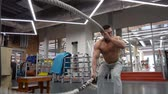 undulation : Sportsman doing heavy rope training at the gym