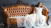 girlish : Pregnant young bride in luxurious dress is sitting on leather couch